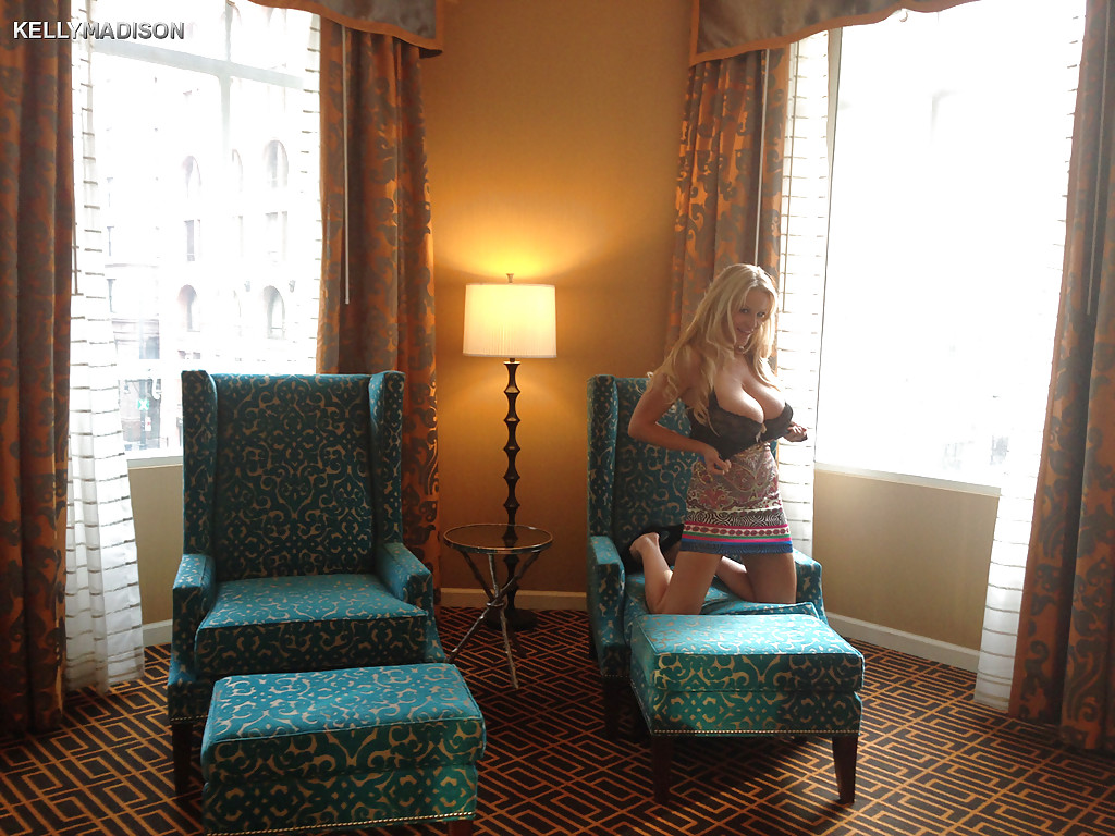 Большегрудая модель со свелыми волосами обнажается в кресле гостиной